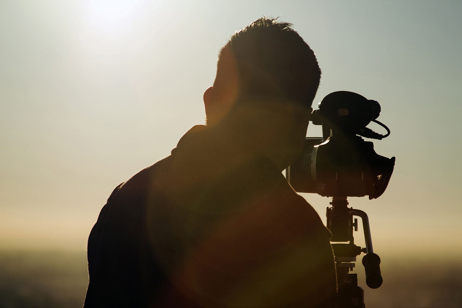 Aspiring Filmmaker shoots a time lapse outdoor in beautiful weather with sun rays around.